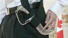 A Montreal teenager displays his kirpan while waiting for a decision from the Supreme Court of Canada in Ottawa on March 2, 2006. (FRED CHARTRAND/The Canadian Press)