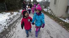 Pupils at Fraser Mustard Early Learning Academy in Toronto walk ahead of their parents and fellow students on Nov. 28, 2013. (DEBORAH BAIC/THE GLOBE AND MAIL)