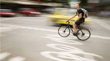 A cyclist makes his way along the bike lane at the corner of Hornby Street and Robson Street in Vancouver on June 27, 2011. (John Lehmann//The Globe and Mail/John Lehmann//The Globe and Mail)