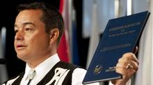 National Chief Shawn Atleo holds up an agreement signed between First Nations and the Soci�t� Nationale de l'Acadie as he delivers his opening address at the 32nd Annual General Assembly of the Assembly of First Nations in Moncton, NB on Tuesday July 12, 2011. (David Smith/THE CANADIAN PRESS)