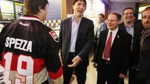 Liberal Party Leader Justin Trudeau, middle, and Liberal MP Kevin Lamoureux, right, joke with an Ottawa Senators supporter at a food court in downtown Winnipeg on May 2, 2013. (JOHN WOODS/THE CANADIAN PRESS)