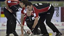 Ontario skip Glenn Howard (C) watches the line of his shot as teammates Craig Savill (R) and Brent Laing sweep during play against New Brunswick at the Canadian Men's Curling Championships in Edmonton, Alberta March 6, 2013. (ANDY CLARK/REUTERS)