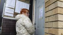 Rebekah Caverhill enters her Calgary rental property on Sept. 30, 2013, after a follower of the Freemen-on-the-Land movement was arrested and removed from the home. (JEFF McINTOSH/THE CANADIAN PRESS)