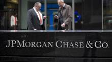 Businessmen check their mobile phones in front of JPMorgan Chase & Co. offices in New York, in this file photo. (Scott Eells/Bloomberg)