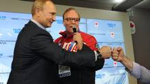 Russian President Vladimir Putin, left, is greeted while visiting Canada House during the 2014 Winter Olympics, Friday, Feb. 14, 2014 in Sochi, Russia. (MIKHAIL KLIMENTYEV/AP)