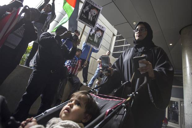 A woman and child, at Los Angeles International Airport on Saturday, pass near demonstrators who support a court ruling that grants a nationwide temporary restraining order against Donald Trump's presidential order to ban immigration to the United States from seven Muslim-majority countries.