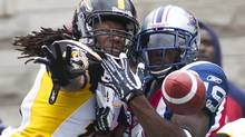 Hamilton Tiger-Cats' Woodny Turenne, left, interrupts a pass for Montreal Alouettes' S.J. Green during the first half of their CFL football game in Montreal on Sunday. (CHRISTINNE MUSCHI)