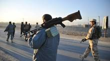 Afghan security forces patrol the site where Taliban suicide bombers attacked a joint U.S.-Afghan air base in Jalalabad, east of Kabul, Afghanistan, Sunday, Dec. 2, 2012. Taliban suicide bombers attacked early Sunday, detonating explosives at the gate and sparking a gun battle that lasted at least two hours with American helicopters firing down at militants before the attackers were defeated. (Nasrullah Khan/AP)
