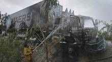 A firefighter sprays water on a truck which was set ablaze by gunmen in Quetta July 11, 2011. Six men on three motorbikes fired on a NATO truck carrying supplies for foreign troops in Afghanistan. (REUTERS/REUTERS)