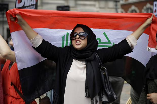 A British Iraqi protester holds up an Iraqi flag outside the Queen Elizabeth II Conference Centre in London on July 6, 2016.