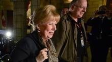 Senator Pamela Wallin is escorted by assistant Mark Fisher as she arrives at the Senate on Parliament Hill in Ottawa on Wednesday, Oct. 23, 2013.