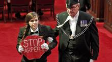 A Senate page is escorted out of the chamber as the Governor-General delivers the Speech from the Throne in Ottawa on June 3, 2011. (CHRIS WATTIE/REUTERS)