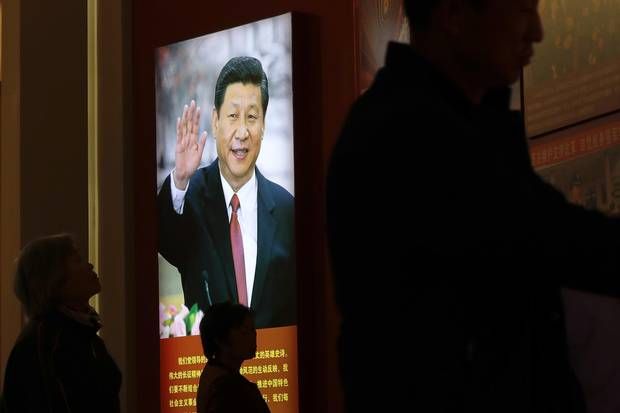 Visitors walk by an image of Mr. Xi at an exhibition on the Long March at the military museum in Beijing on Oct. 24, 2016.