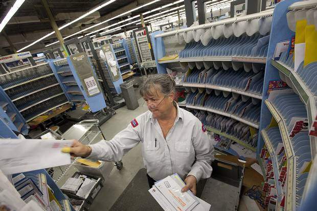 Canada Post employee Donna Yerxa sorts mail for her delivery route in Scarborough on Dec. 13, 2013.