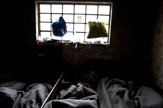 A migrant sleeps on the ground under a window of an abandoned warehouse in Belgrade.