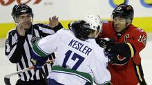 Vancouver Canucks' Ryan Kesler (C) and Calgary Flames' Jarome Iginla mix it up during second period action as Linesmen Shane Heyer (L) tries to break them up in their NHL hockey game in Calgary, Alberta, April 5 , 2012. (JACK CUSANO/REUTERS)