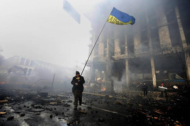 An anti-government protester holds a Ukranian flag as he advances through burning barricades in Kiev's Independence Square on February 20, 2014. The protests led to the ousting of embattled pro-Russia Ukrainian President Victor Yanukovich.