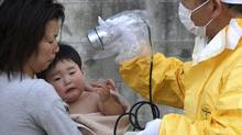 A one-year-old boy is re-checked for radiation exposure after being decontaminated in Nihonmatsu, Fukushiima, northern Japan Monday. (Toru Nakata/Toru Nakata/AP)