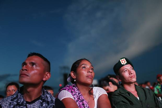 FARC rebels watch the signing broadcast at an encampment in the remote Yari plains.