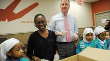 Mayor Bill de Blasio, middle, and New York City's first lady, Chirlane McCray, mark the Martin Luther King Jr. holiday by bagging meals with Girl Scouts from Brooklyn Troop 2260 at the Distribution Community Kitchen and Food Pantry in run by New York's Food Bank the Food Bank in New York's Harlem neighborhood, Jan. 20, 2014. (Susan Watts/AP)