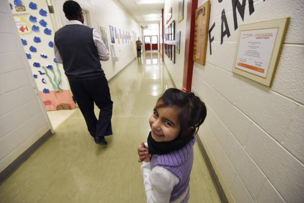 Five year old Mariah Al Rassoul follows Iroquois Junior Public School principal Marcia Pate to her first day in kindergarten class in Toronto. Six Syrian refugee children joined the school on Jan. 4, 2016 after arriving in Canada a month earlier.