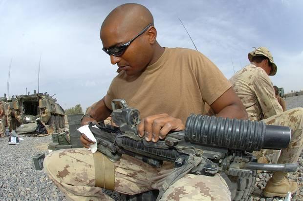 Master Corporal Charles Matiru cleans his rifle.