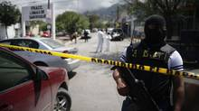 A federal police officer stands behind the line at a crime scene in the municipality of Guadalupe in Monterrey, April 10, 2012. Gunmen had shot dead seven taxi drivers on the outskirts of Monterrey, which has become one of Mexico's most violent cities during a turf war between rival drug cartels. (Daniel Becerrill/Reuters/Daniel Becerrill/Reuters)