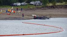 Crews prepare a boom on the Gleniffer reservoir to stop oil from a pipeline leak near Sundre, Alta., on Friday, June 8, 2012. Plains Midstream Canada says one of their non-functioning pipelines leaked between 1,000-3,000 barrels of oil. (Jeff McIntosh/THE CANADIAN PRESS)