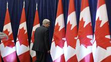 Prime Minister Stephen Harper leaves after a news conference on Parliament Hill Friday regarding rules on foreign investment. (CHRIS WATTIE/REUTERS)