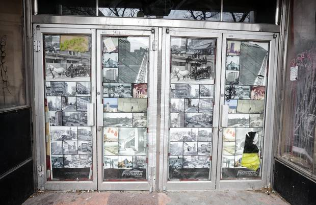 A closed storefront downtown displays pictures of Hamilton's past.