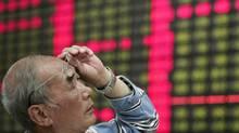 An investor looks at the stock price monitor at a private securities company in Shanghai on Monday. Chinese shares lost ground Monday, with the benchmark Shanghai Composite Index falling 2.73 per cent, or 64.89 points, in its biggest drop in terms of points this year, to 2,308.55. (Associated Press)