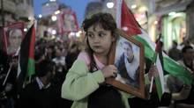 A girl holds a portrait of a Palestinian held in an Israeli jail during celebrations after a deal to end a prisoners hunger strike was agreed, in the West Bank city of Ramallah May 14, 2012. (AMMAR AWAD/REUTERS/AMMAR AWAD/REUTERS)
