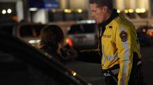 A Victoria police officer prepares to test a driver's blood-alcohol level during a check stop on Yates Street in downtown Victoria in November 2011. (Chad Hipolito for The Globe and Mail)