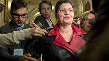 Quebec Liberal MLA Fatima Houda-Pepin is surrounded by reporters as she walks to a party caucus meeting on Jan. 20, 2014. (JACQUES BOISSINOT/THE CANADIAN PRESS)