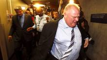 Toronto Mayor Rob Ford runs from cameras after exiting an executive council meeting in Toronto, March 19, 2014. Ford, who made global headlines last year after admitting he had smoked crack cocaine, was caught up in fresh controversy on Monday after a new video showed him agitated and apparently swearing outside city hall.