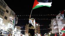 A Palestinian boy in traditional clothes waves a Palestinian flag during a rally in the West Bank city of Ramallah on Nov. 29, 2012. The 193-nation U.N. General Assembly overwhelmingly approved a resolution that same day to upgrade the Palestinian Authority's observer status at the United Nations. (MARKO DJURICA/REUTERS)