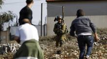 An Israeli soldier, middle, shouts as he holds his weapon in front of Palestinian during clashes in Jalazoun refugee camp near the West Bank city of Ramallah, January 31, 2014. (MOHAMAD TOROKMAN/REUTERS)
