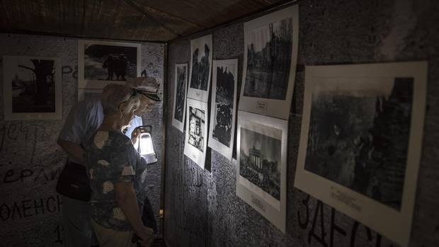 Visitors examine Second World War photographs in a military tent installed in a park in Perm as part of the city's Kaleidoscope festival.
