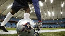 In this file photo, Montreal Alouettes Timothy Strickland picks-up his helmet during practice at B.C. Stadium in Vancouver November 23, 2005. (JOHN LEHMANN/The Globe and Mail)