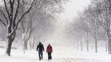Rolling Meadows High School students Jack Swindells, 14, and Connor Allen, 15, walkwith their heads down to shield themselves from the blowing snow in Arlington Heights, Ill., Tuesday, Feb. 26, 2013. The students were dismissed early as a winter storm moved through the Northwest suburbs of Chicago. (Mark Welsh/AP)