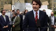 Liberal Leader Justin Trudeau holds a press conference on Parliament Hill in Ottawa on Wednesday June 5, 2013., as a small group of protesters are seen in the background. (Sean Kilpatrick/THE CANADIAN PRESS)