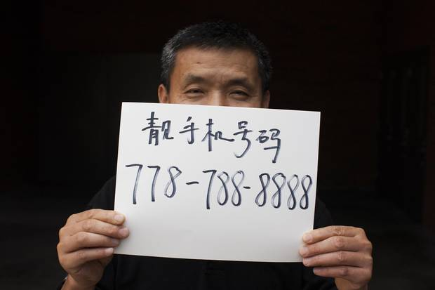 Howard Xu is seen holding up a paper with his lucky phone number.