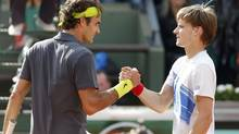 Roger Federer of Switzerland (L) shakes hands with David Goffin of Belgium after winning his match during the French Open tennis tournament at the Roland Garros stadium in Paris June 3, 2012. (GONZALO FUENTES/REUTERS)