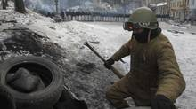 A protester in Kiev reinforces a barricade with a line of riot police in the background, Feb. 1, 2014. Ukraine's embattled president Viktor Yanukovych is taking sick leave as the country's political crisis continues without signs of resolution. (Sergei Chuzavkov/AP)