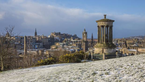 A view over the city of Edinburgh with the Dugald Stewart Monument in the foreground.