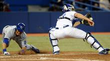 Kansas City Royals right fielder Nori Aoki dives safely across the plate to score as Toronto Blue Jays catcher Josh Thole takes the throw in the fifth inning at Rogers Centre. (USA TODAY Sports)