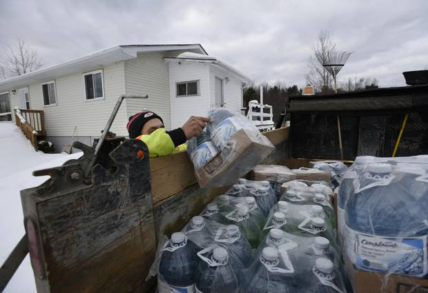 Marvin McLeod reaches for bottles of water while making deliveries to homes on the Serpent River First Nation on Dec. 21, 2016.