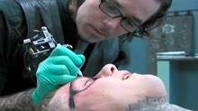 A man gets a pair of Ray-Ban glasses tattooed on his face. (Never Hide Films)
