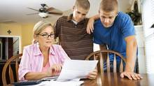 Mother and sons paying bills. (Jupiterimages/Photos.com)