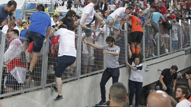 Spectators try to escape from Russian supporters who went on a charge in the stands right after the Euro 2016 Group B soccer match between England and Russia, at the Velodrome stadium in Marseille, France.